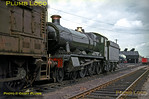 """GWR """"Hall"""" Class 4-6-0 No. 6938 """"Corndean Hall"""" has had its nameplate removed but its brass and copper work is highly polished and the paintwork gleams. It is not in steam and is being shunted around the depot at Southall by a filthy Class 08 0-6-0DE shunter. Another """"Hall"""" lets off steam outside the shed building in the background. Sunday 13th June 1965. Slide No. 1363."""